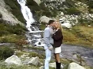 Tourists have oral fun in mountains near waterfall